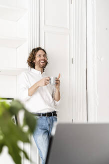 Happy man drinking coffee at home - GIOF07495