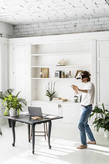 Man at home using VR glasses - GIOF07507