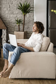 Man using laptop on couch at home - GIOF07519