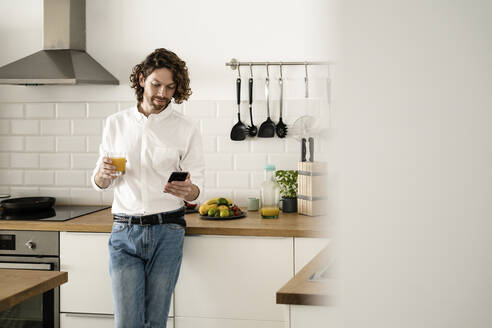 Man holding glass of orange juice and cell phone in kitchen at home - GIOF07525