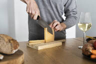 Close-up of man cutting cheese on kitchen counter - GIOF07528
