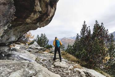 Hiker walking through alpine plateau in autumn, Sondrio, Italy - MCVF00065