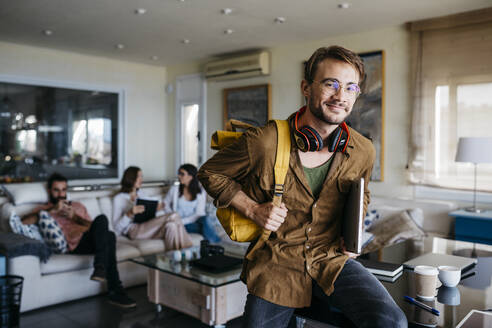 Portrait of smiling man with backpack, headphones and laptop with friends in background - JRFF03834
