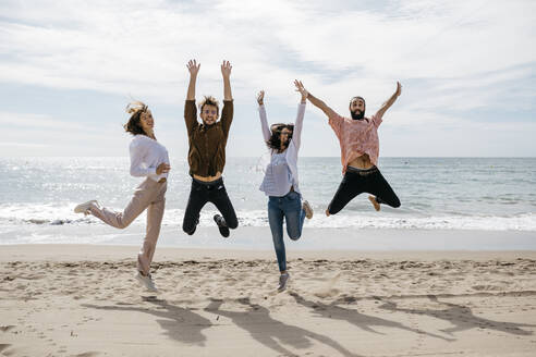 Exuberant friends jumping on the beach - JRFF03846