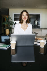 Portrait of smiling woman working on table at home with laptop - JRFF03873