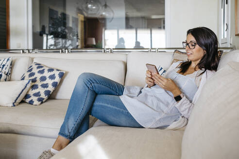 Smiling woman at home sitting on couch looking at cell phone - JRFF03888