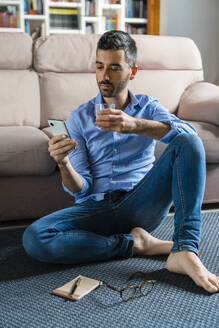 Portrait of young man sitting barefoot on the floor of living room at home looking at smartphone - MGIF00822