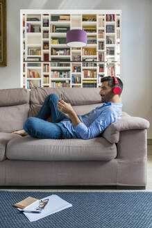 Smiling young man lying on the couch at home using smartphone and wireless headphones - MGIF00831