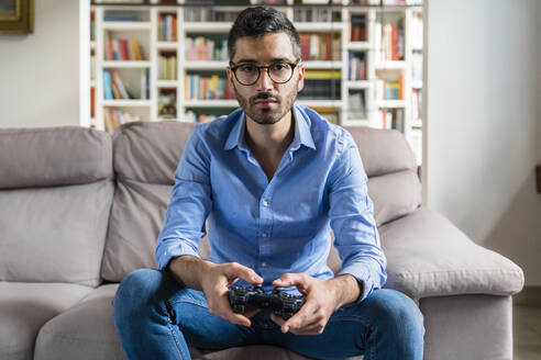 Portrait of serious young man sitting on the couch at home playing video game - MGIF00840