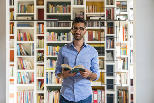 Portrait of smiling young man with book standing in front of bookshelves at home - MGIF00843