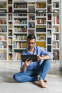 Portrait of barefoot young man sitting in front of bookshelves on the floor using digital tablet - MGIF00849
