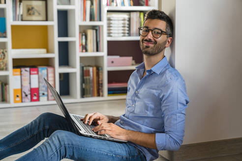 Portrait of smiling young man sitting on the floor at home using laptop - MGIF00855