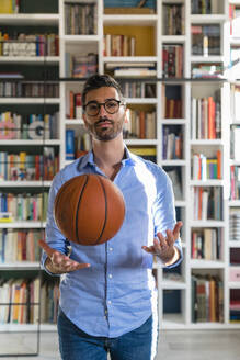 Portrait of young man with basketball standing in front of bookshelves at home - MGIF00858