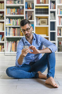 Portrait of smiling young man sitting in front of bookshelves on the floor at home using smartphone - MGIF00864
