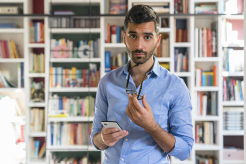 Portrait of sceptical young man with smartphone standing in front of bookshelves - MGIF00867
