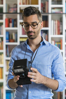 Portrait of young man standing in front of bookshelves looking at instant camera - MGIF00876