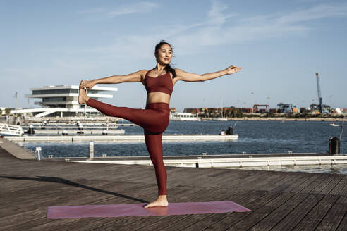 Asian woman practicing yoga, standing on one leg, hand-to-big-toe pose - RCPF00085