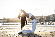 Asian woman practicing yoga on a pier at harbour at sunset, camel pose - RCPF00100