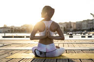 Rear view of Asian woman practicing yoga on a pier at harbour in the evening - RCPF00106