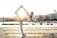 Asian woman practicing yoga on a pier at harbour at sunset, dancer pose - RCPF00112