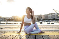 Asian woman practicing yoga on a pier at harbour, half-spinal twist at sunset - RCPF00115