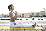 Asian woman practicing yoga on a pier at harbour - RCPF00118