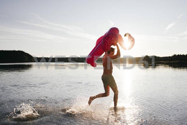Young man running with flamingo pool float into a lake - EYAF00650 - Ekaterina Yakunina/Westend61
