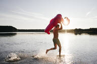 Young man running with flamingo pool float into a lake - EYAF00650