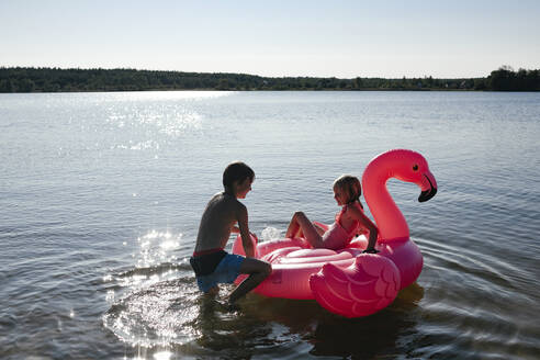 Brother and sister with flamingo pool float on the lake - EYAF00653