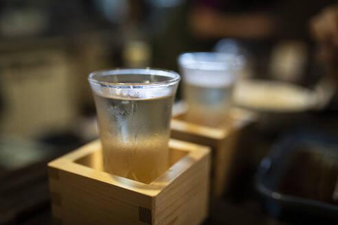 Japan, Takayama, Sake served in masu in traditional Japanese restaurant - ABZF02709