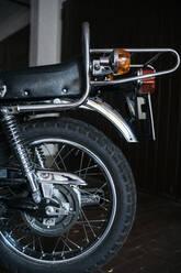 Back wheel of vintage motorbike parked in garage - JPIF00236