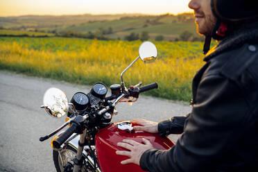 Crop shot of man on his vintage motorbike at sunset, Tuscany, Italy - JPIF00242
