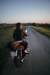 Back view of young woman sitting on motorbike at sunset looking at view, Tuscany, Italy - JPIF00245