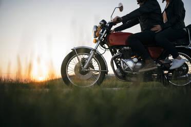 Crop shot of couple on vintage motorbike at sunset - JPIF00248