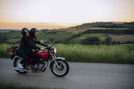 Young couple riding vintage motorbike on country road at sunset, Tuscany, Italy - JPIF00251