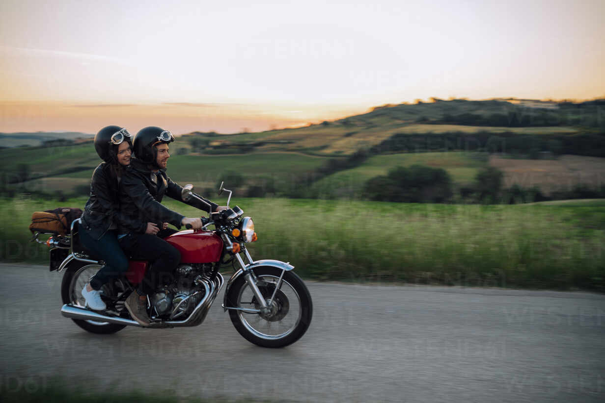 Young couple riding vintage motorbike on country road at sunset, Tuscany, Italy - JPIF00251 - Juri Pozzi/Westend61