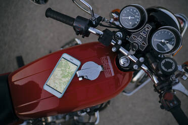 Smartphone with road map lying on tank of vintage motorbike, top view - JPI00254