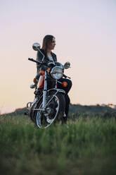 Young woman with vintage motorbike in rural scene enjoying sunset - JPIF00257