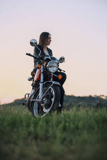 Young woman with vintage motorbike in rural scene enjoying sunset - JPIF00257