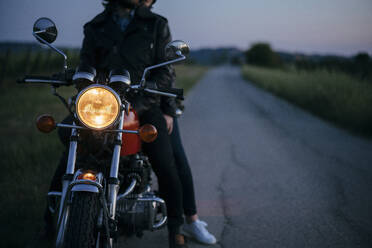 Crop shot of young couple on vintage motorbike at roadside - JPIF00260