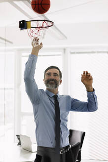 Happy mature businessman playing basketball in office - MOEF02514