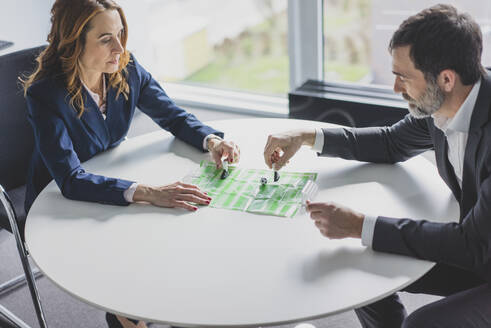 Businesswoman and businessman playing table football in office - MOEF02541
