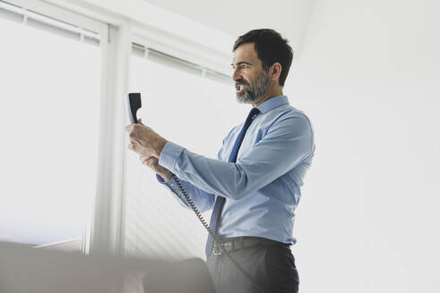 Angry mature businessman holding telephone receiver in office - MOEF02547