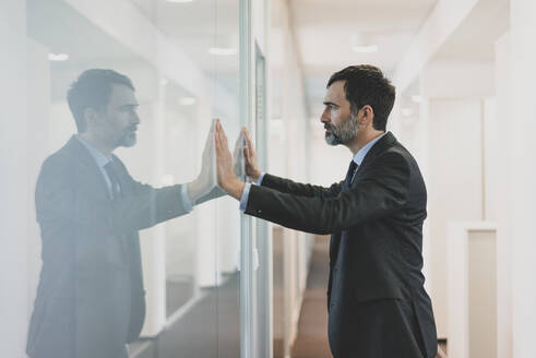 Thoughtful mature businessman leaning against glass wall in office - MOEF02553