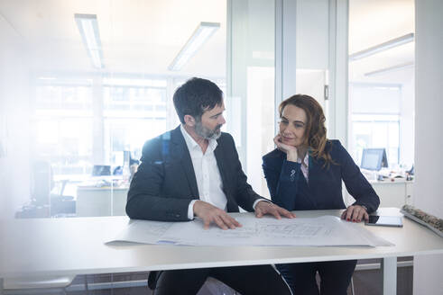 Businesswoman and businessman working on plan on desk in office - MOEF02574
