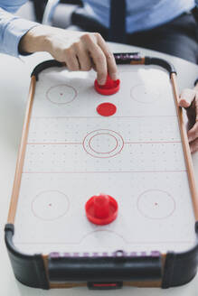 Close-up of businessman playing air hockey - MOEF02577