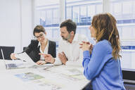 Businessman and two businesswomen working together at desk in office - MOEF02586