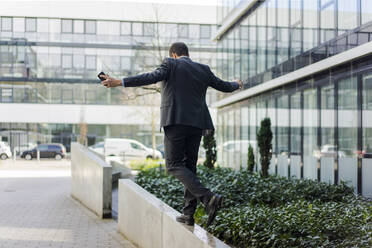 Rear view of businessman balancing on a wall outside office building - MOEF02610
