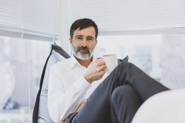 Portrait of mature businessman having a coffee break - MOEF02625
