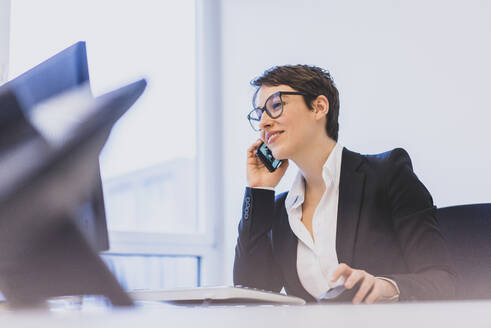 Young businesswoman on the phone at desk in office - MOEF02631